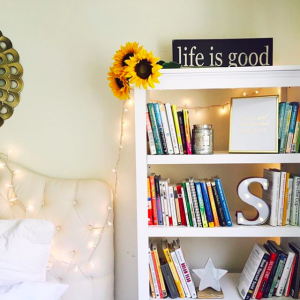 room with books fairy lights sunflowers and a life is good sign