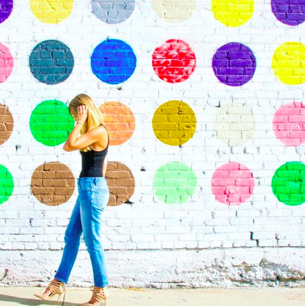 blonde girl in jeans in front of a colorful wall with dots