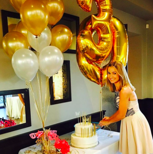birthday girl with a white cute cake and white and gold balloons
