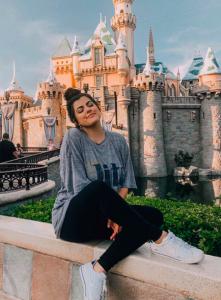 brunette girl smiling in front of a castle