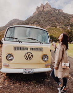 brunette girl in front of a Wolkswagen van at the mountains