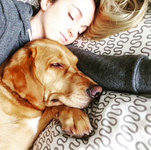Girl sleeping with her puppy dog