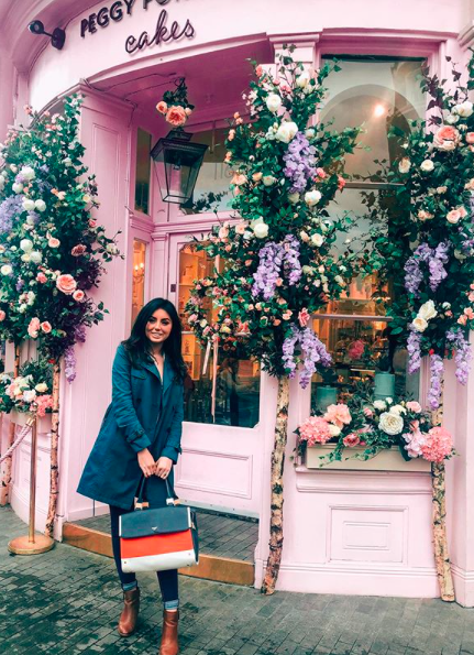 Girl in front of a store covered in flowers in the UK