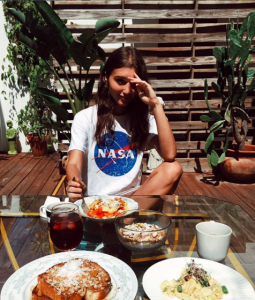 girl with a lot of food in New York in a Nasa tee