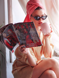 Girl reading Vogue with a pink cup