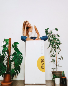 Blonde girl sitting at the top of a box with green plants