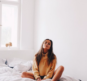 Girl on her bed with white walls